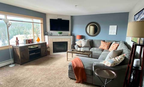 Enjoy beautiful views and open floor plan from the cozy living room with a smart tv and gas fireplace.