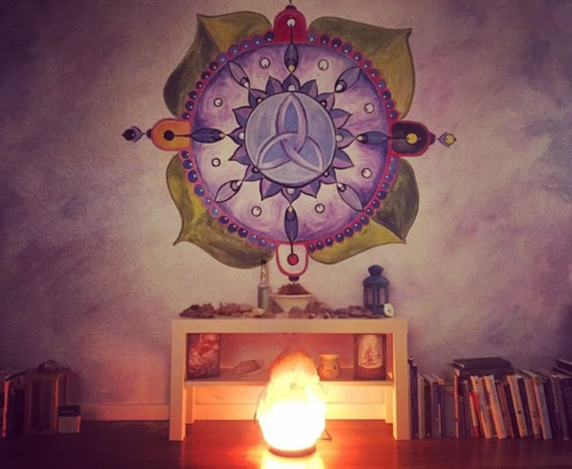 Our cozy living room with hand painted mural, altar space you are welcome to use, salt lamps, and lots of books!