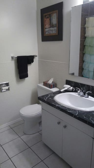 This is the shared main bathroom.  It has a full tub and shower.  There is a hairdryer for you to use, just ask if you need a straightener or a curling iron too.  Shampoo, conditioner and body wash is on the rack in the shower.