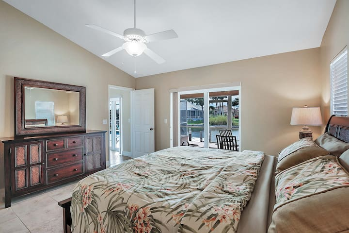 Dramatic king-sized master bedroom with large double windowed doors leading out onto the patio and water. Island living at its finest!