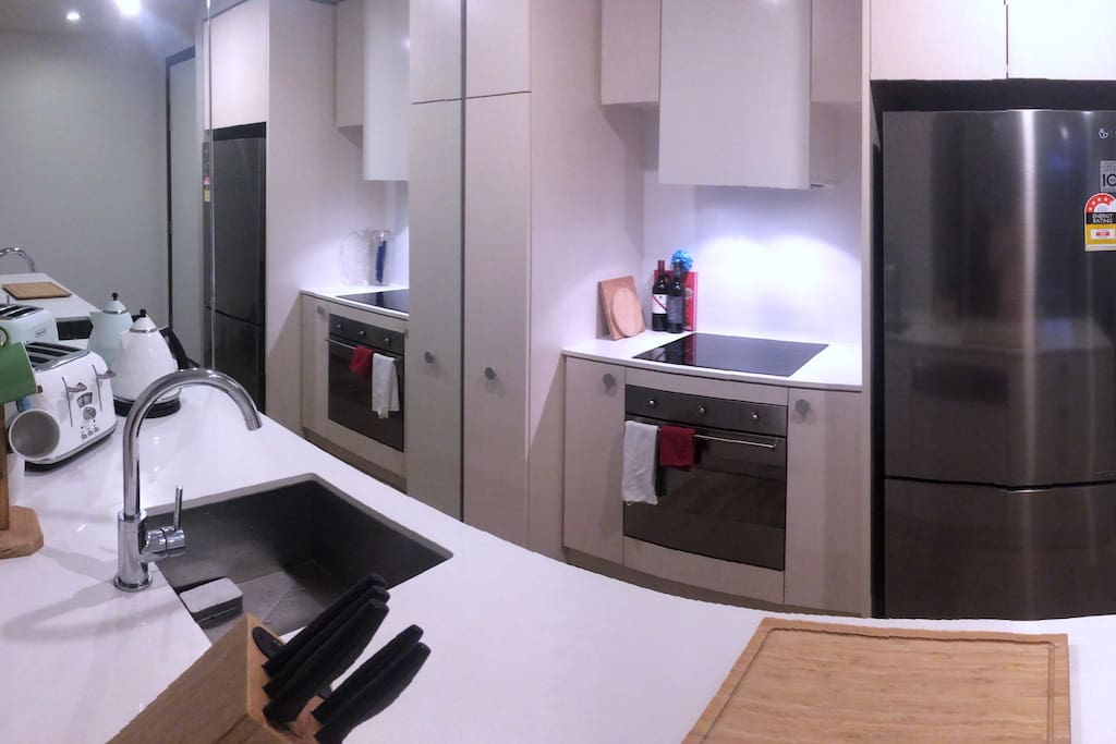 Kitchen with electric stove and oven, dishwasher, toaster, kettle and fridge.