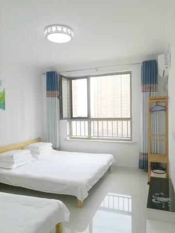 主卧:配有衣帽架、空调、拖鞋、床头柜,从窗户往外可以看到蔚蓝的大海。