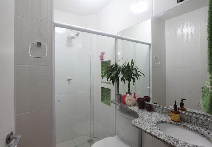 Banheiro com box de vidro e um espelho bem grande!