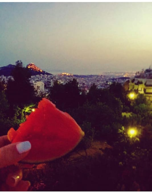Balcony view -Lycabettus, Acropolis and the sea- at dusk