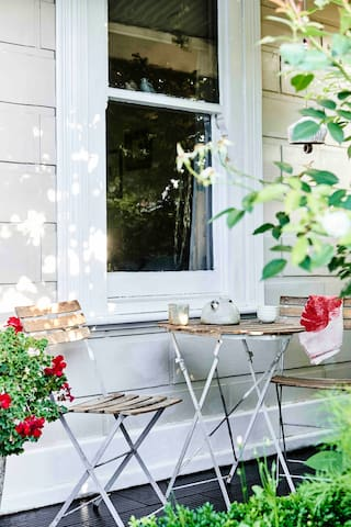 Sunny front porch with leafy green garden.