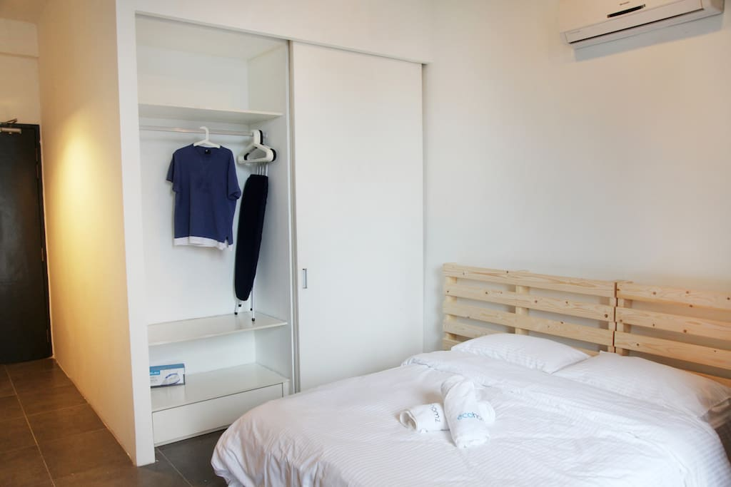 A Wardrobe next to the 1 queen size bed. Iron and Ironing board is provided.
