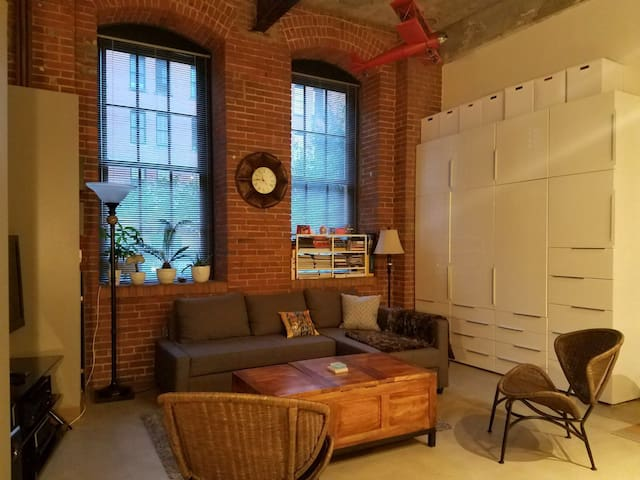 Unit has high ceilings and exposed brick walls.