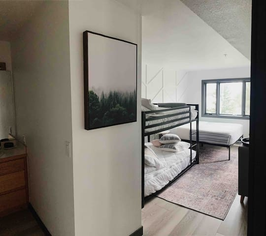 Spacious 2nd bedroom furnished with full over full bunks dressed with Beddys linens. + Queen. Views off this bedroom are perfection and also has its own private door to and from patio.  - New flooring, paint, trim, hardware, furnishings and linens!