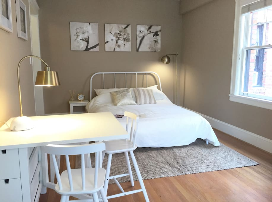 View of first half of studio: Featuring queen bed and dining/work table