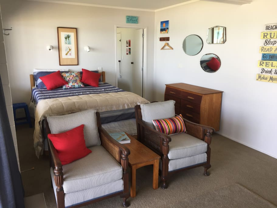The living area and queen bed with the door to the  bedroom on the right-side of the bed..
