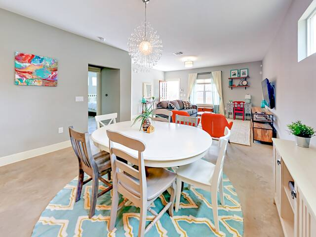 The dining and living areas have bright natural light and modern decor. A wooden dining table seats 6.