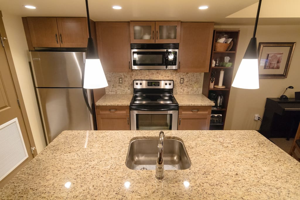 Fully equipped kitchen with new appliances and quartz counters.