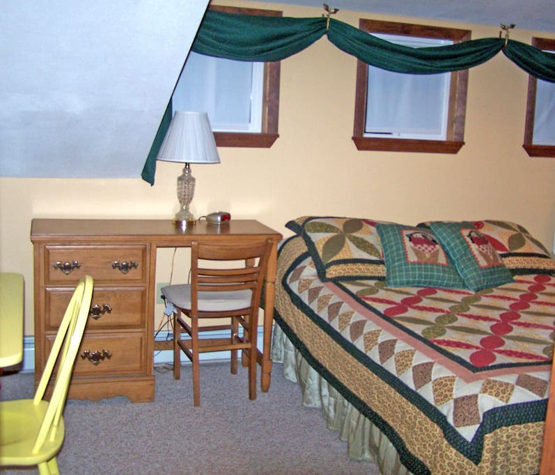 McIntosh Suite with a queen bed and two single beds, and private bathroom with shower/tub.