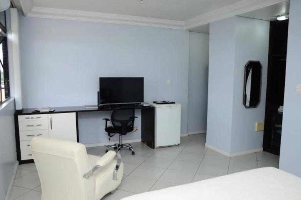 Bancada com TV flat screen, frigobar, gavetas e cadeira para usar laptop.