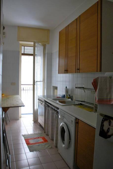 cucina con elettrodomestici e terrazzina con tavolino per colazioni