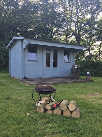 Log Cabin With It's Decking Area And Fire Pit