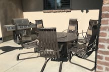 Shared outdoor BBQ grill and patio with table and chairs