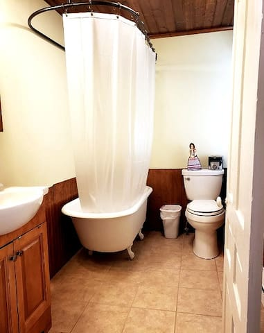 Claw foot tub, shower, and commode in the adjoining common area are available to guests.