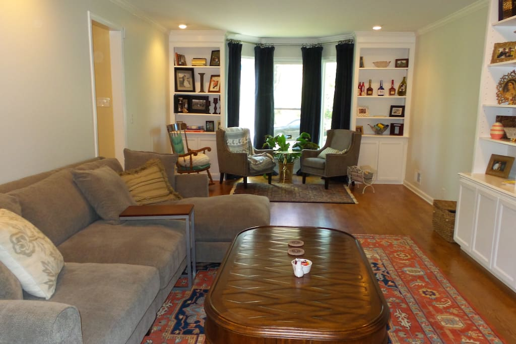 Large den - showing large sectional, bay window sitting area, and bookshelves.