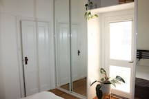 Two large sliding wardrobes with mirrors and a door which leads to a small private courtyard