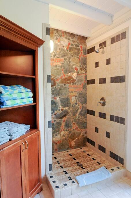 The en suite baths have stone and tile showers