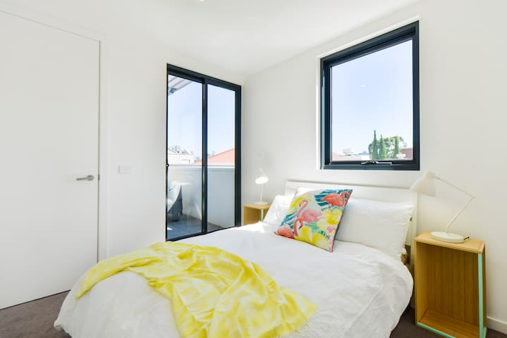 The bedroom is complete with a queen bed, a window, wardrobe for storage and access to the private balcony