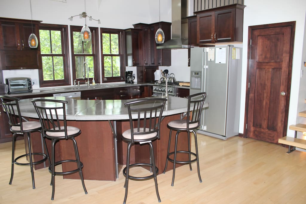 Expansive, custom, gourmet kitchen with immaculate concrete counter tops, a center island with available seating and modern architectural lighting, making it a perfect place for gatherings. The kitchen sits adjacent to the dinning room, seating for up to 10 more people.