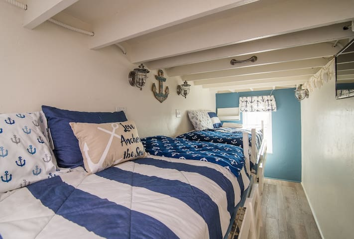 two twin beds in bright nautical themed space with ocean view