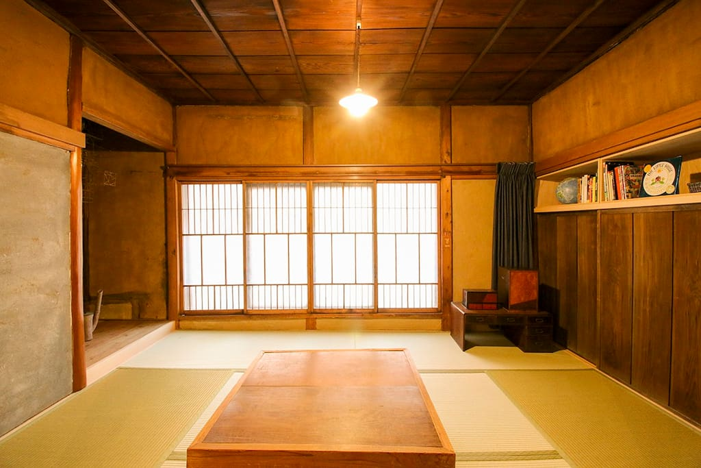 The living room has tatami, original dirt walls and windows, a traditional heated kotatsu table and two futon that may be used for additional guests