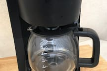 Coffee maker with coffee, cups, and filters provided