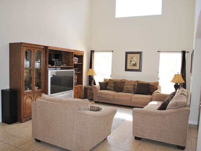 Large sitting room with lots of seating and large screen TV