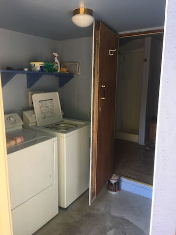 Washer/dryer and full bathroom with hot water, toilet and sink.