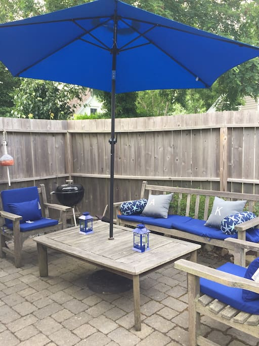 Backyard enclosed patio area with grill and umbrella for shade perfect for entertaining