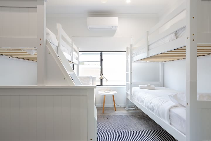 The bunk room is a very flexible sleeping space. On one side we have a double bed on the bottom, which is comfortable and can sleep up 2 adults, above and opposite are 3 single beds. So this room is capable of sleeping, 5 people.