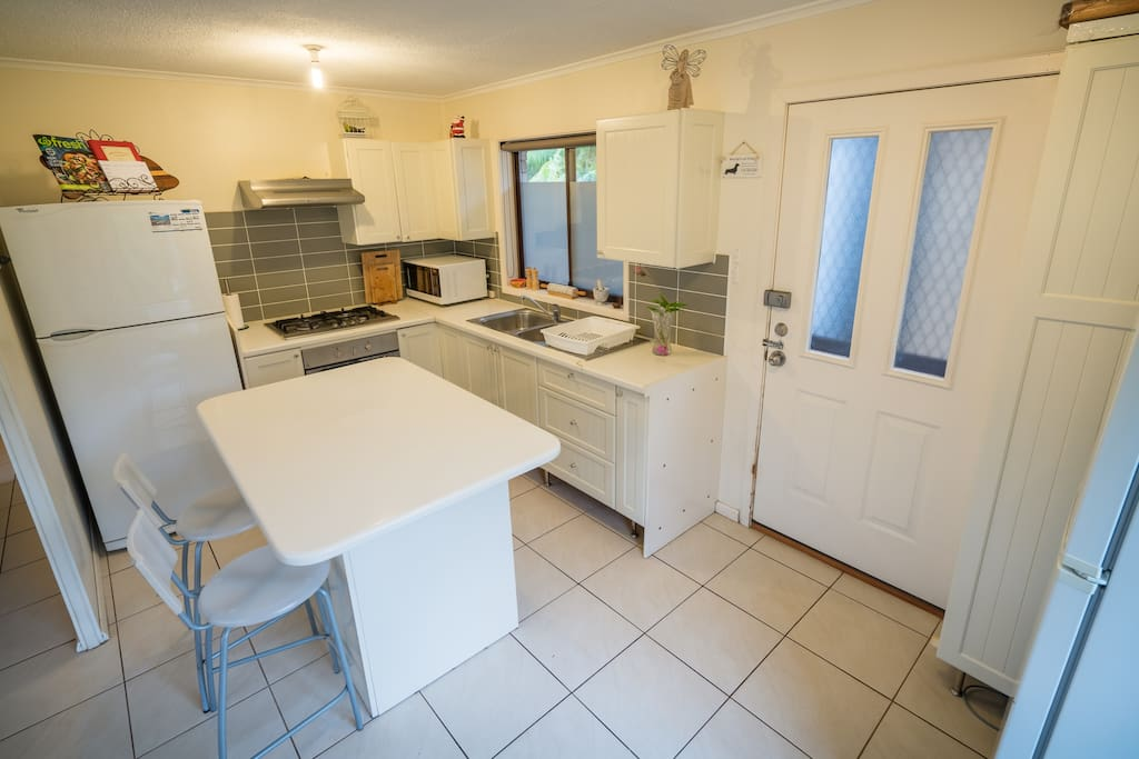Kitchen featuring twin sink, oven, cooktop, fridge/freezer and cupboards