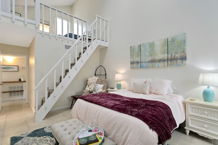 A queen sized bed with a loft and 2 twins