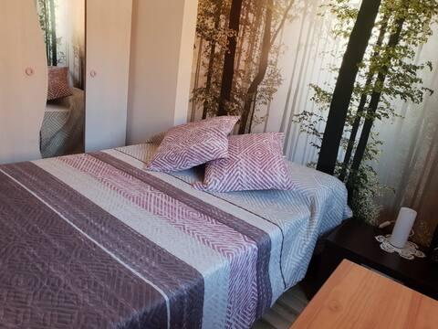 habitación de cama de matrimonio, con armario, mesa y mesita, con tv, y ventana con persiana y cortina, mucha luz
