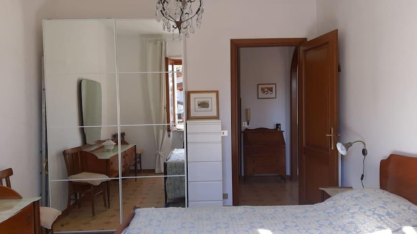 Camera da letto matrimoniale spaziosa e luminosa con vista sul giardino privato.