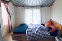 Tầng ngủ với chiếc giường ngay cửa sổ đón nắng sáng và nhìn xuống sân