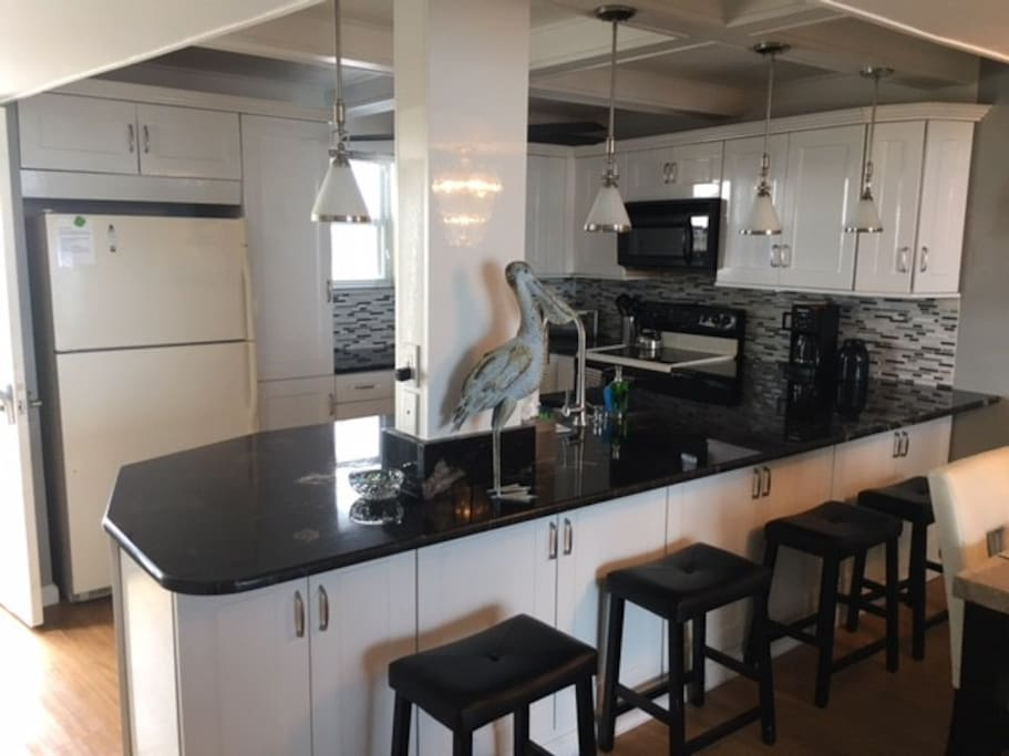 Updated kitchen with extra large granite breakfast bar, full dishwasher, stove/oven, microwave. Stocked with plenty of cookware, glassware, silverware, and more. Full size washer and dryer located off kitchen.