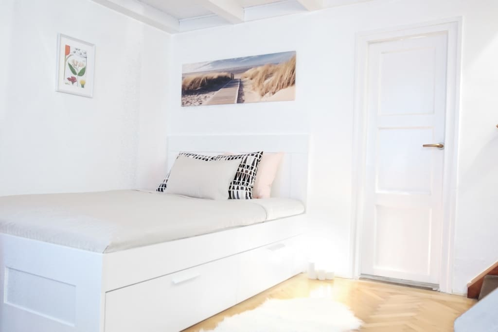 The downstairs bedroom area with queen size bed and storage space underneath.