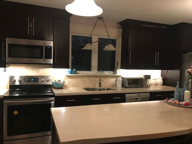 Fully equipped kitchen with fridge, microwave, oven, and dishwasher. Dishes, pots, pans, and cooking supplies along with silverware is available to guests.