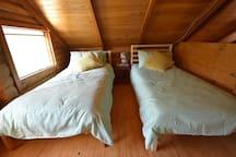 Two single beds in the sleeping loft.