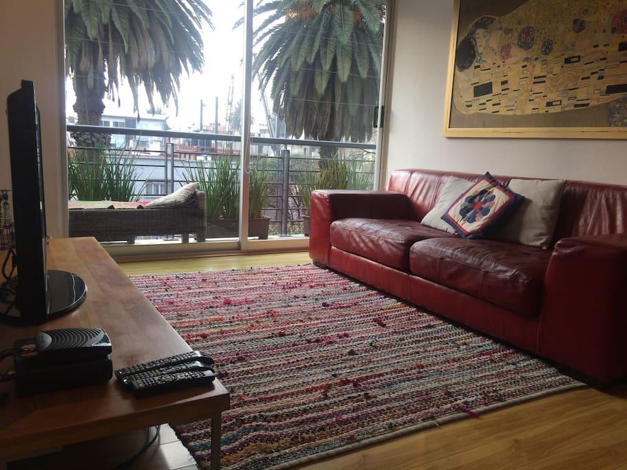 Sala estancia con decoración contemporánea, sofá de piel, tv y vista exterior  y salida al balcón.