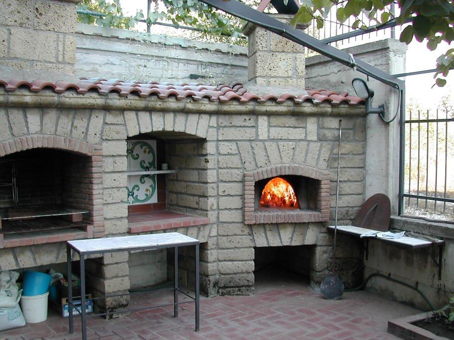 Al livello inferiore c'è un'altro spazio ampio dove si trova un forno per pizze e una grande griglia per barbecue con piano d'appoggio centrale. D'estate la pianta di kiwi cresce arrampicandosi al pergolato dando una piacevole ombra.