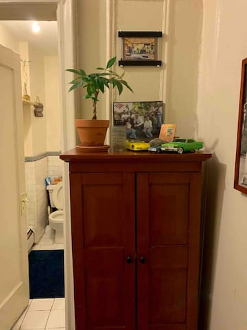 Entrance to bathroom has a freshly washed towel and linen closet.