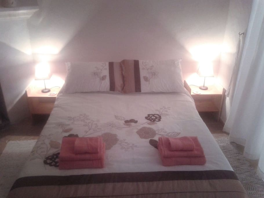 A comfortable double bed with bed side tables and lamps