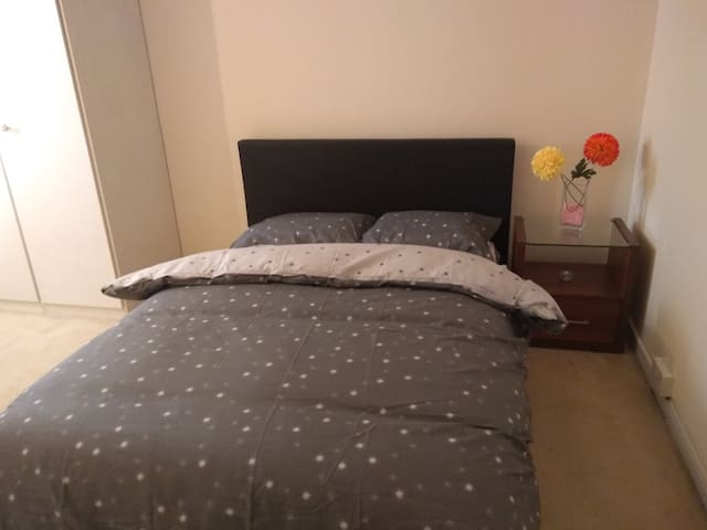 Large bedroom with integrated wardrobes & side table