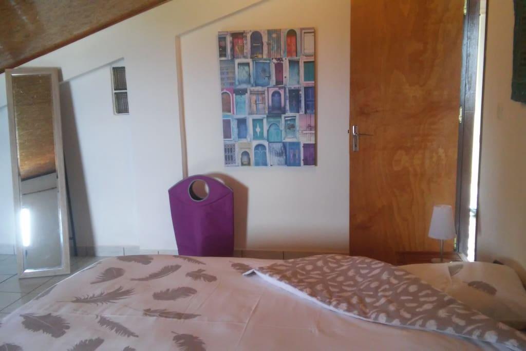 grande chambre parentale, avec lit 160, petite table et chaises pouvant faire office de bureau,penderie, meuble pour vêtements.