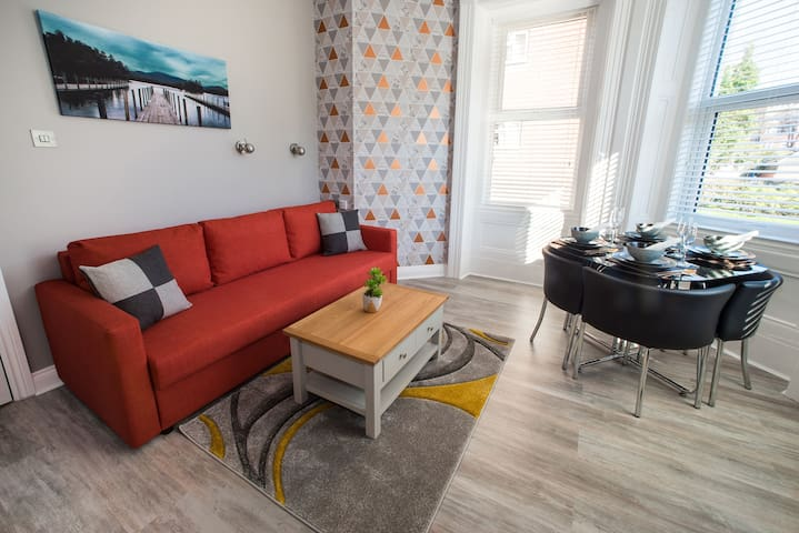 The living area includes a comfortable sofa, coffee table and rug